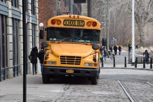 Photo of a yellow school bus parked near a building.
